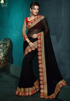 Set yourself apart from the crowd in this bold and vivacious black faux georgette saree designed with zari, dori, sequins and patch border work.  #Sari #Georgette(fabric) #Blouse #Zari #Artsilk #Sequin #Yarn | Elena